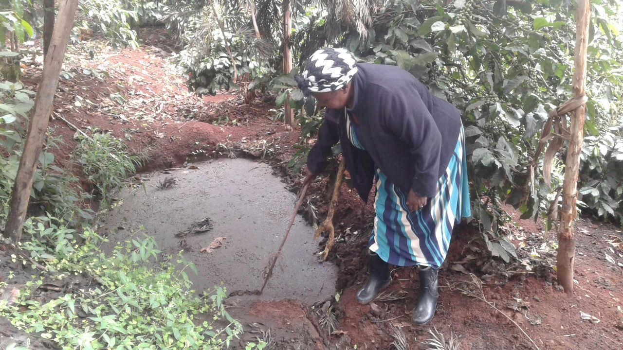 Dionesia Ireri stirs the cow dung mixture that she transforms into biogas with the help of a biodigester. Credit: SNV.